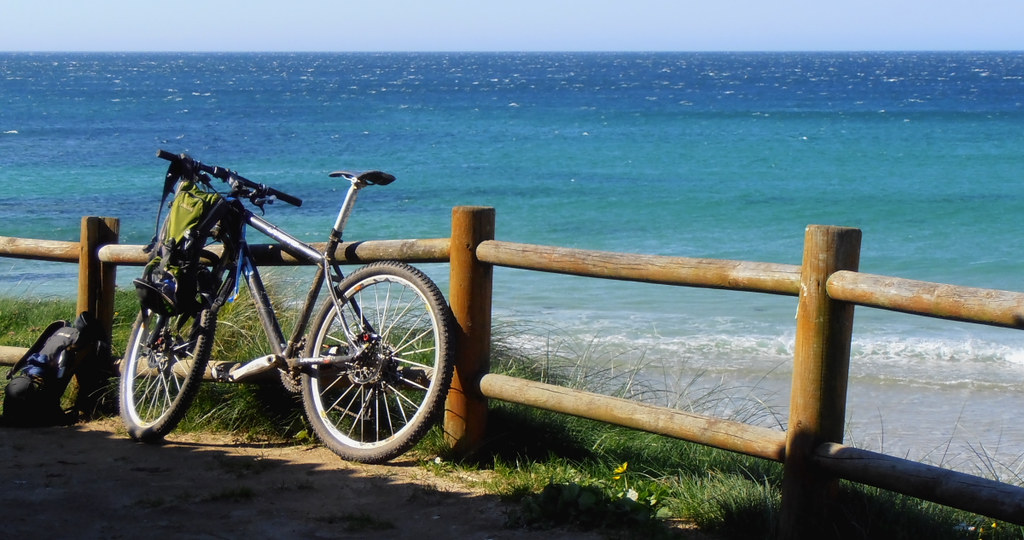 Una biciletta adagiata sulla staccionata che divide la terraferma dal mare