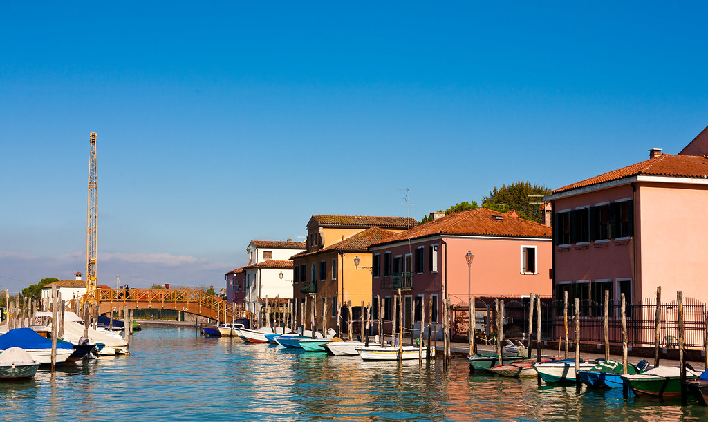 a canal with boats in Torcello, along with houses that are on it
