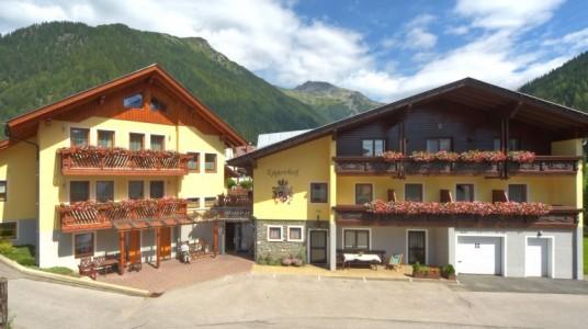 Hotel visto dall'esterno, con montagne in sottofondo e una bellissima facciata fiorita