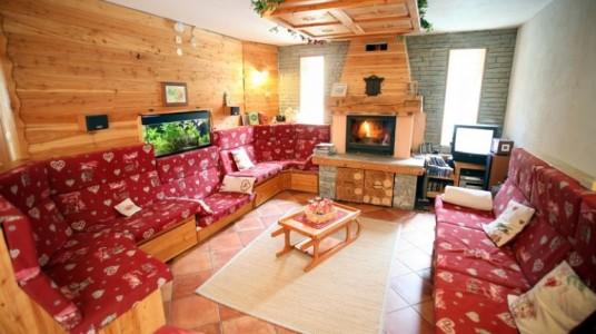 hall dello chalet con mobilio interamente in legno e un piccolo caminetto acceso