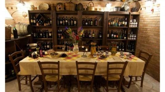 sala ristorante hotel con vini esposti e tavola imbandita