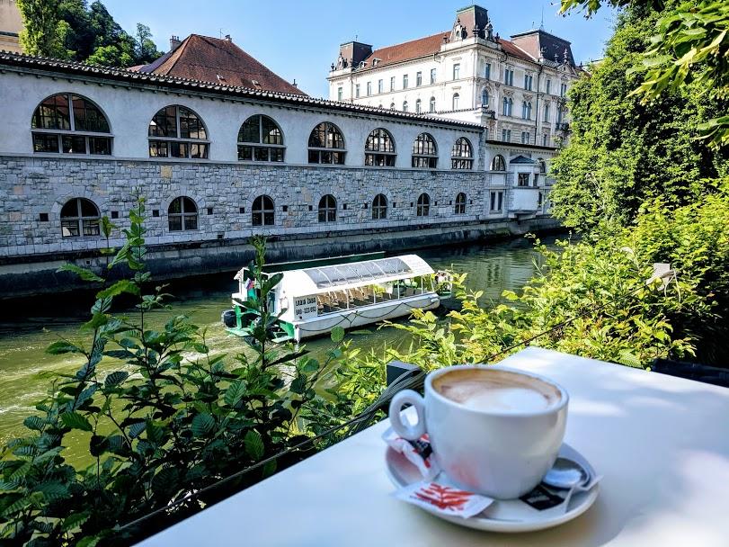Vista del fiume Ljubljanica con tavolo e cappuccino