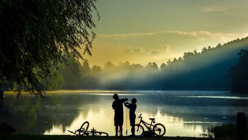 bambini e biciclette in riva ad un lago