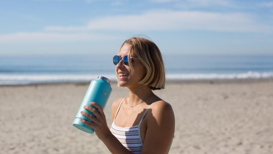 ragazza sulla spiaggia che sta bevendo dalla borraccia