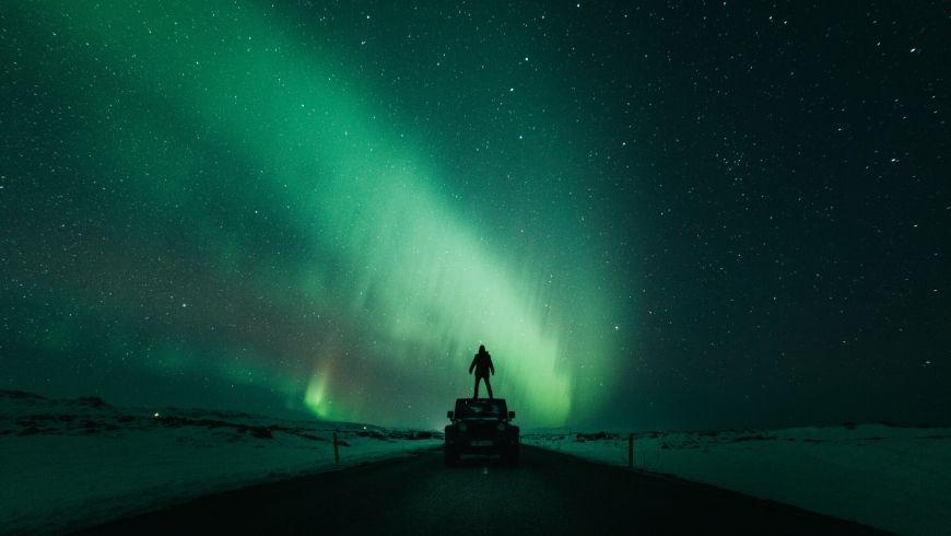 uomo davanti all'aurora boreale