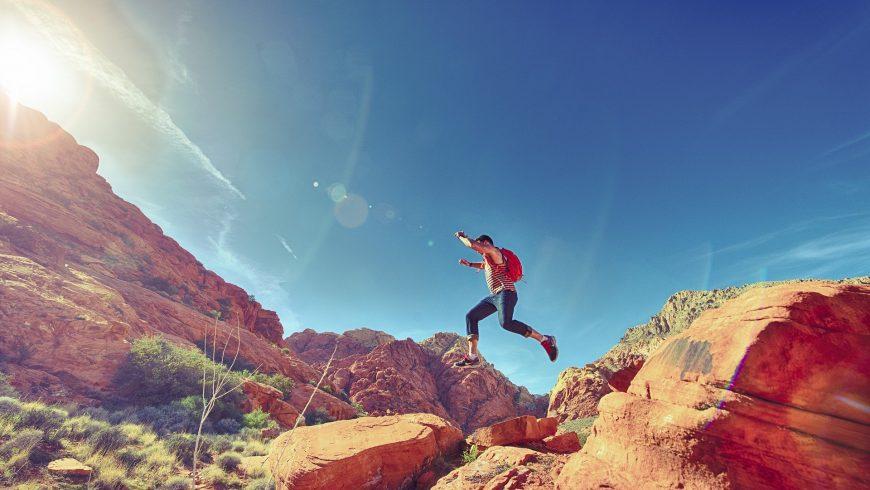 Uomo che salta sulle rocce durante un'escursione