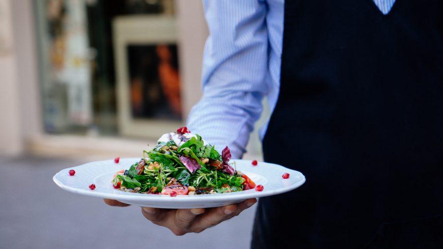 Cameriere che porta un piatto di insalata senza glutine