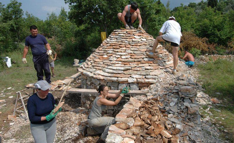 Costruzione di una capanna di pietra tradizionale nel Kazun park