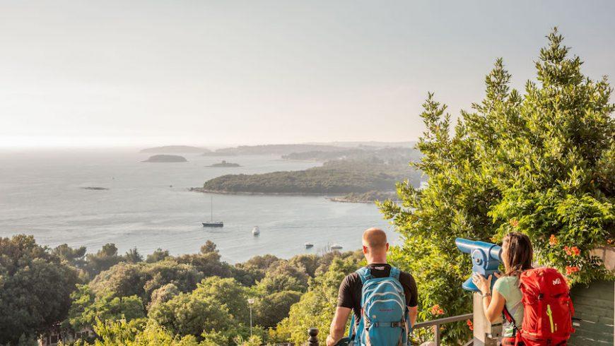 Coppia osservando il panorama da un binocolo durante il viaggio green in Istria