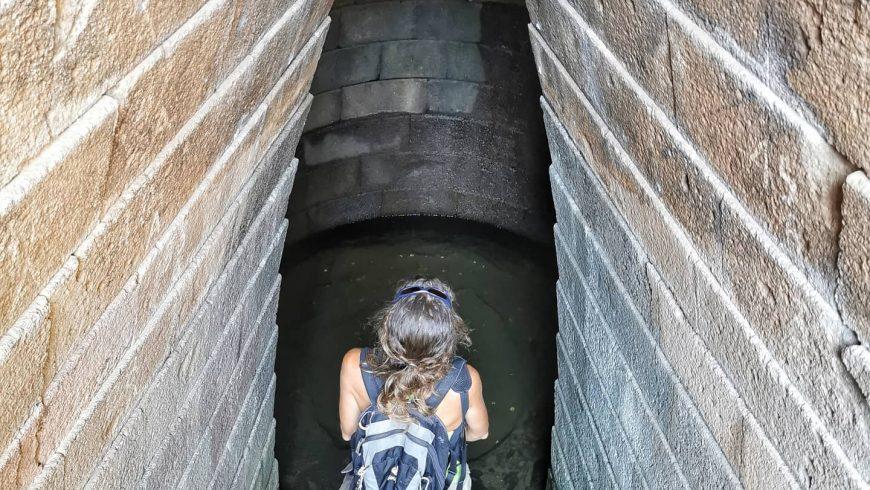 Viaggiatrice di spalle sulle scale del pozzo sacro