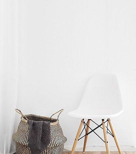 Sedia bianca e cesta con sfondo bianco