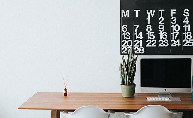 Ufficio minimalista con scrivania di legno e calendario