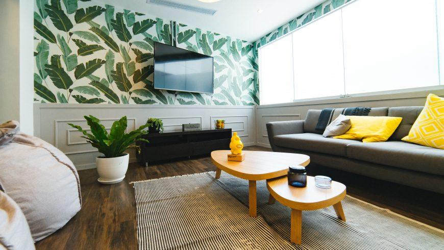 Arredare eco-friendly la casa: divano, piante e parete con foglie verdi