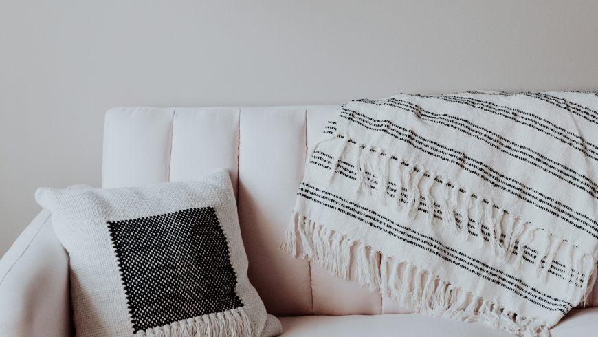 Divano bianco con cuscino e coperta stampati