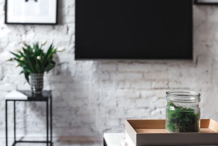 Salotto minimalista con tavolini da caffè, quadri e tv