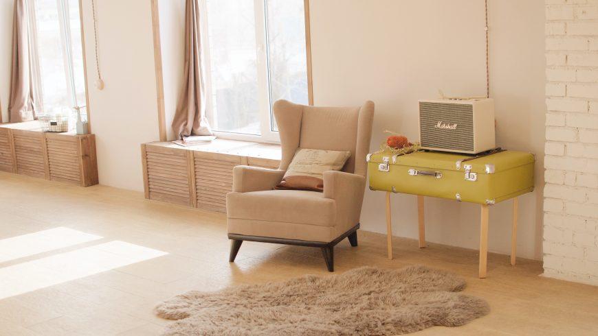 Stanza luminosa con poltrona e valigia vintage gialla utilizzata come tavolino