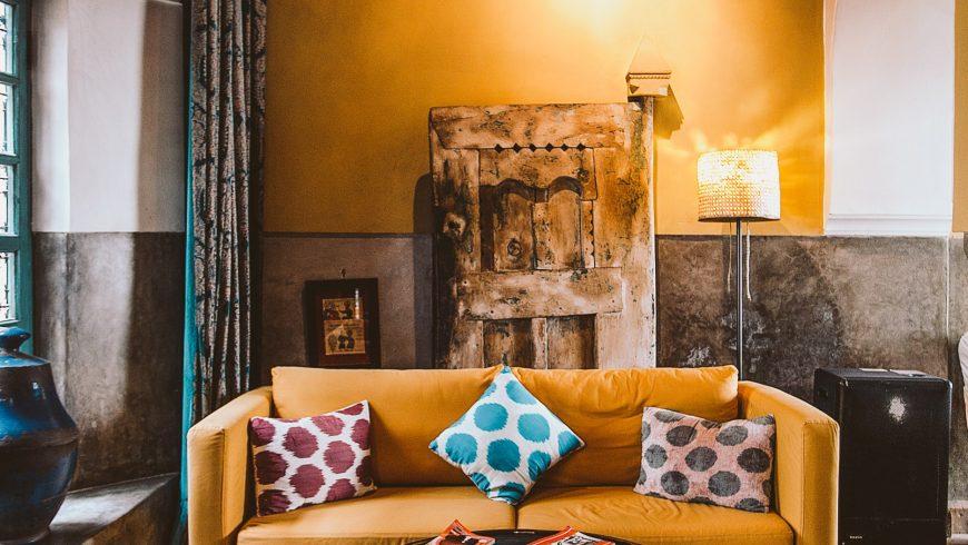 Arredare la casa con mobili artigianali, tra cui un divano arancione con cuscini e una lampada di cristallo