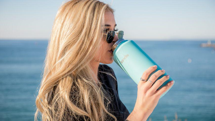 Ragazza che beve da una bottiglia termica, per diventare un viaggiatore sostenibile