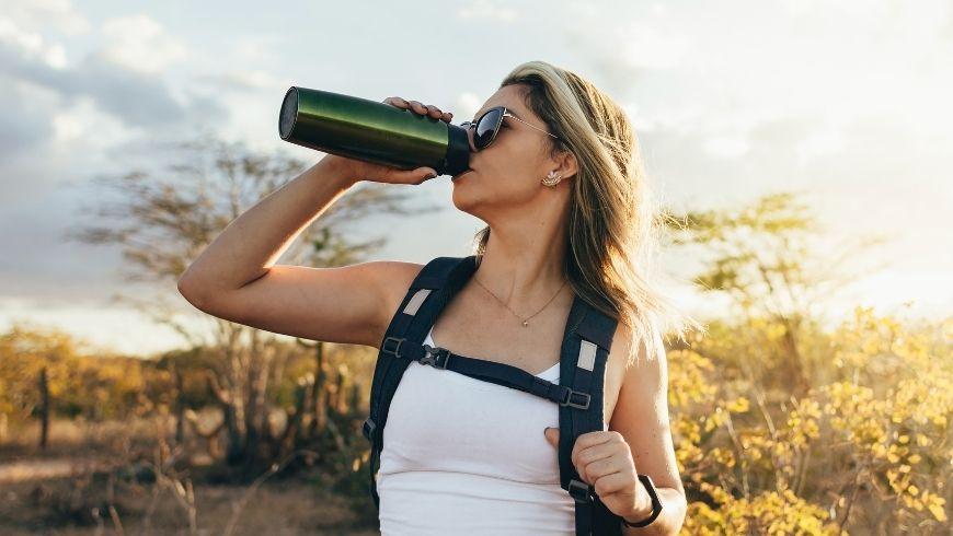Donna che beve l'acqua da una bottiglia termica, per delle abitudini sostenibili