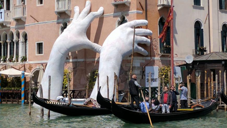 opera d'arte, mani in cemento che sorreggono uno degli edifici piú antichi di Venezia